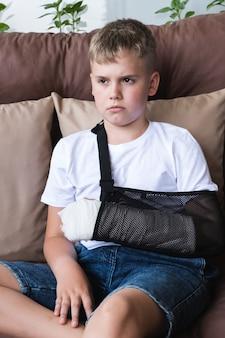Menino triste com braço quebrado engessado sentado em casa na varanda Foto Premium