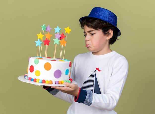 Menino triste com chapéu de festa azul segurando e olhando para um bolo