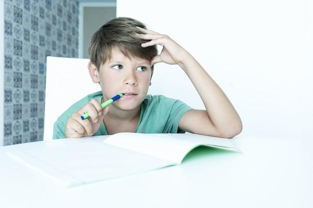 Menino triste com livro faz lição de casa da escola. de volta à escola. estudante infeliz com livros didáticos. ensino à distância.