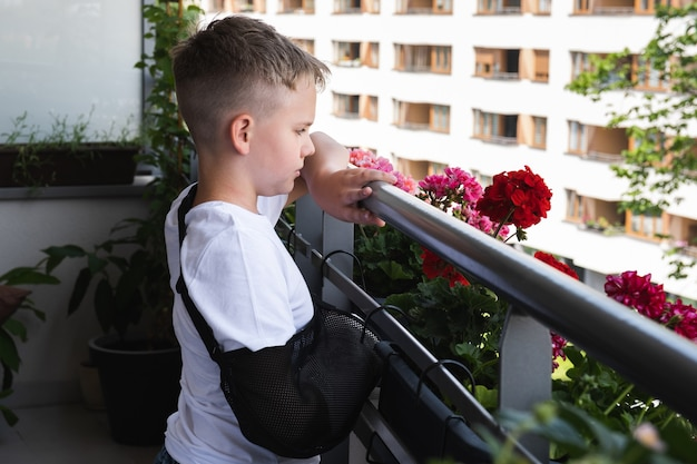 Menino triste com o braço quebrado entediado em casa e olhando para o quintal da varanda
