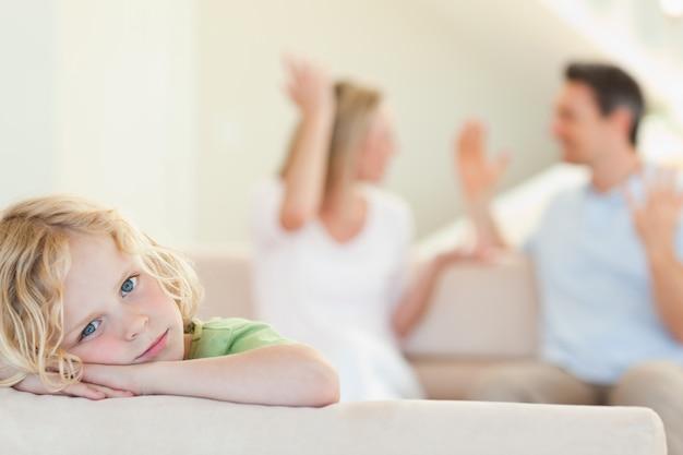 Menino triste com pais lutando ao fundo