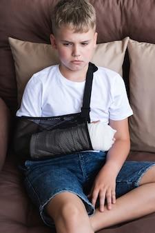 Menino triste com um braço quebrado e feridas na perna gesso na mão de uma criança