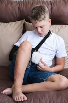 Menino triste com um braço quebrado e feridas na perna sentado em casa na varanda
