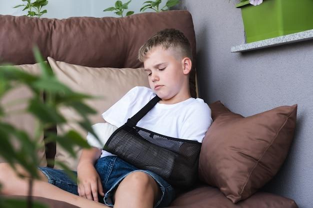 Menino triste com um braço quebrado engessado está entediado em casa