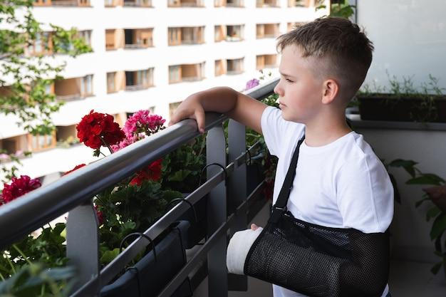 Menino triste com um braço quebrado engessado olhando tristemente para o quintal da varanda