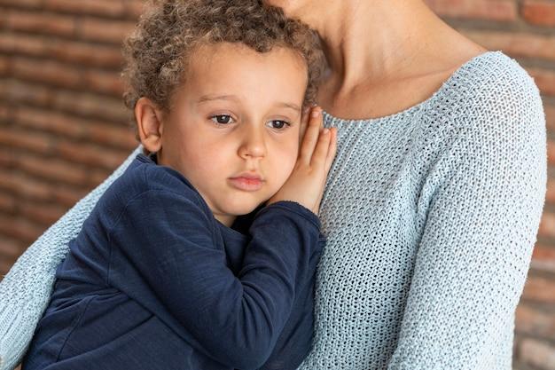 Menino triste consolado pela mãe