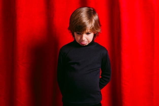 Menino triste de cinco anos, vestindo roupas pretas, contra uma cortina vermelha