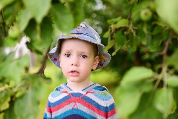 Menino triste em pé no jardim de verão