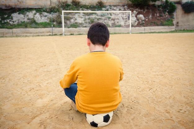 Menino triste, esperando para jogar bola em um campo de futebol velho