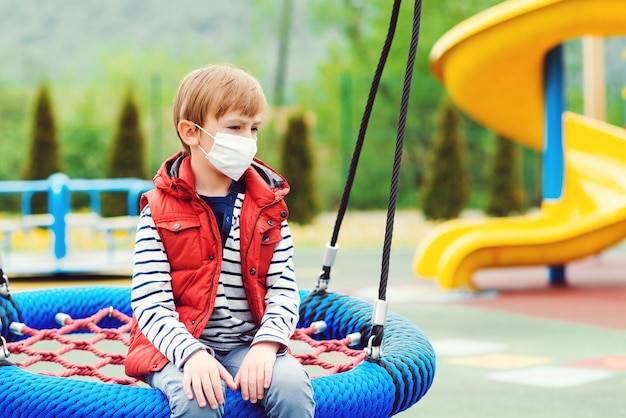 Menino triste na máscara facial sentado no balanço sozinho. criança entediada no playground vazio. quarentena do coronavírus.