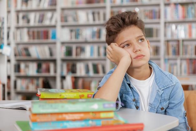 Menino triste, olhando para longe, sentado sozinho na biblioteca na frente de todos os seus livros