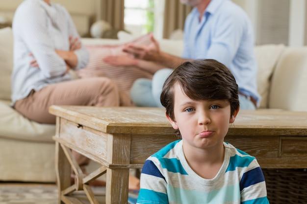 Menino triste, ouvindo seus pais discutindo