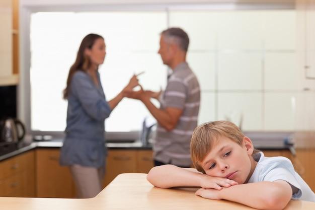 Menino triste ouvindo seus pais discutirem