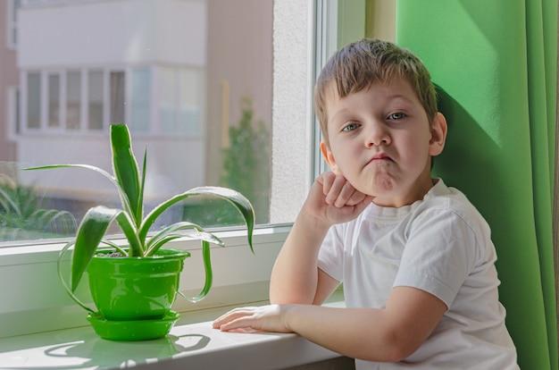 Menino triste quer andar na rua, a criança se senta perto da janela e olha para ele com tristeza. quarentena (auto-isolamento) devido a infecção por coronovírus