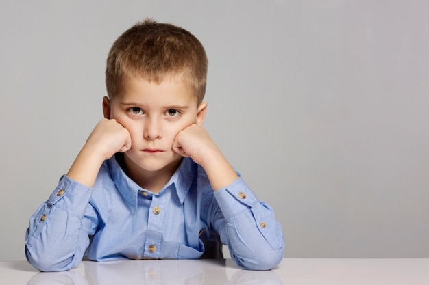 Menino triste senta-se, apoiou a cabeça nas mãos, close-up, cinza