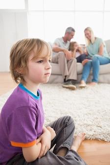 Menino triste sentado no chão enquanto os pais desfrutam com a irmã