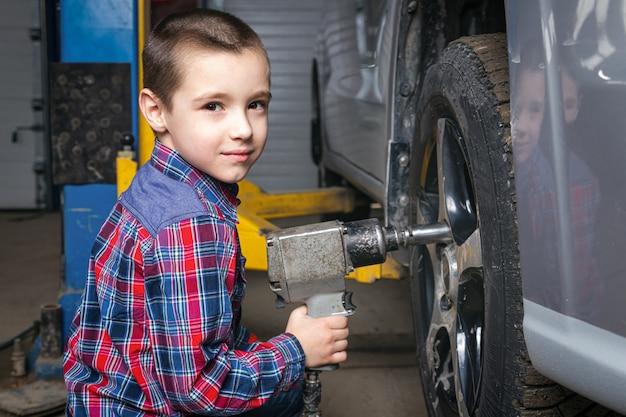Menino, um jovem trabalhador automobilístico, faz uma troca de pneu com uma chave pneumática na garagem de uma estação de serviço. criança aprende os mecânicos mudando de profissão no serviço de reparo de automóveis.