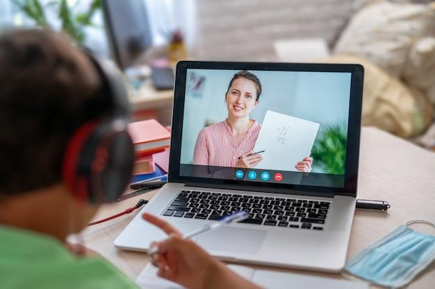 Menino usa laptop para fazer videochamada com o professor
