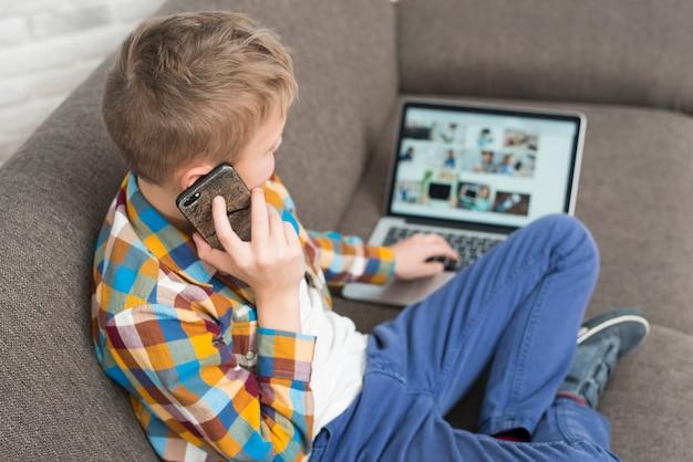 Menino, usando computador portátil, ligado, sofá, e, fazendo telefonema