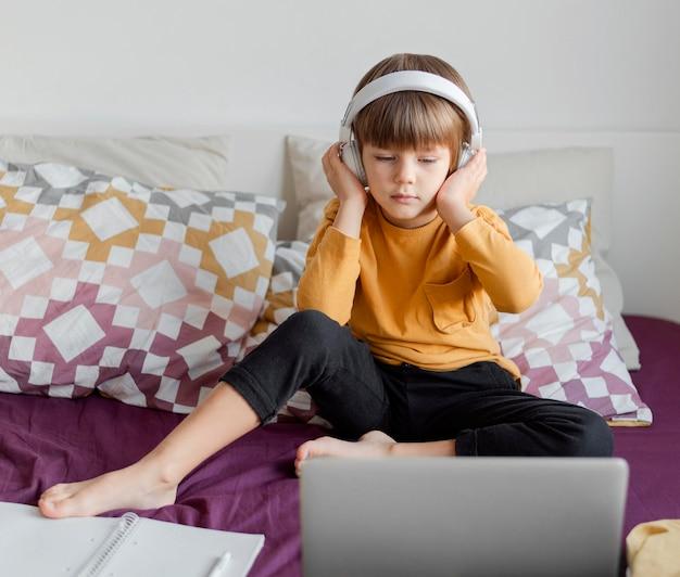 Menino usando fones de ouvido e aprendendo