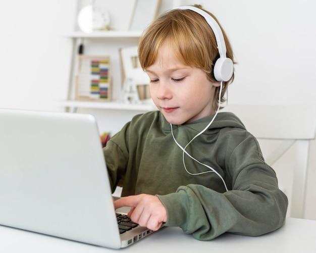Menino usando laptop com fones de ouvido