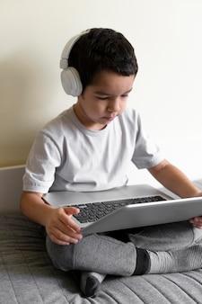 Menino usando laptop na cama com fones de ouvido