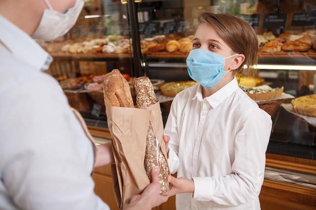 Menino usando máscara médica, comprando pão na padaria durante a pandemia do coronavírus