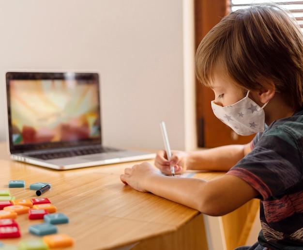Menino usando máscara médica e frequentando uma escola virtual