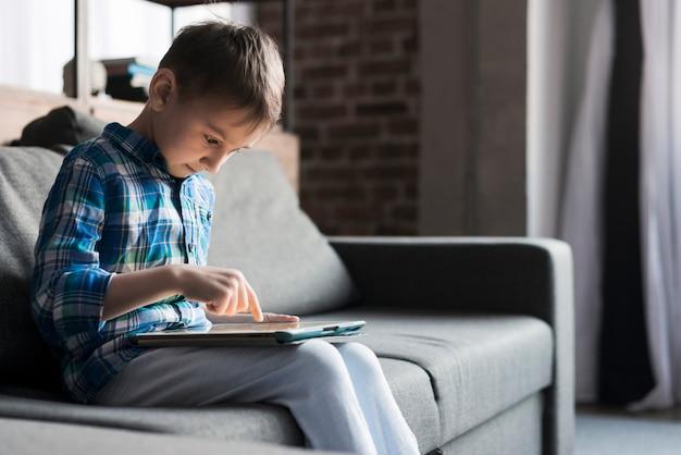 Menino usando o tablet no sofá