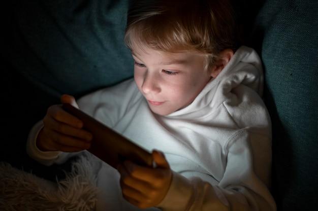 Menino usando smartphone na cama à noite