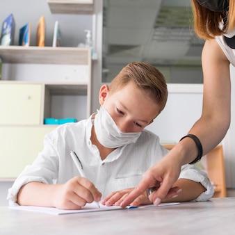 Menino usando uma máscara médica na sala de aula
