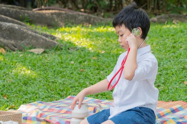 Menino usar estetoscópios e se sentir feliz no parque jardim