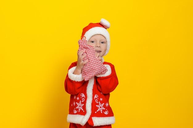 Menino vestido com uma fantasia vermelha de papai noel de ano novo sorri e mostra uma sacola com presentes de que está feliz
