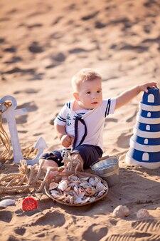 Menino vestido de marinheiro em uma praia com conchas à beira-mar, em uma rede arrastão