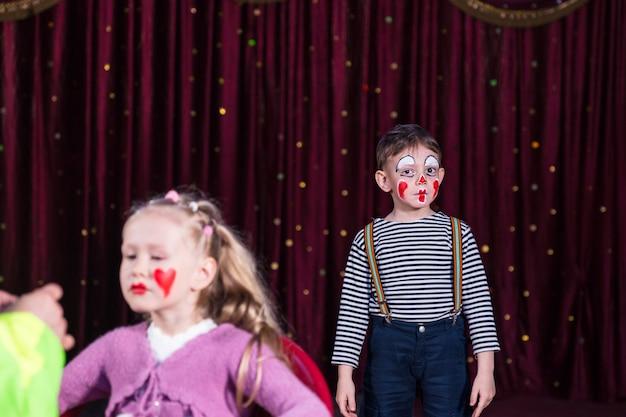 Menino vestido de palhaço usando maquiagem e camisa listrada em pé no palco com cortina vermelha, menina fazendo maquiagem aplicada no rosto em primeiro plano