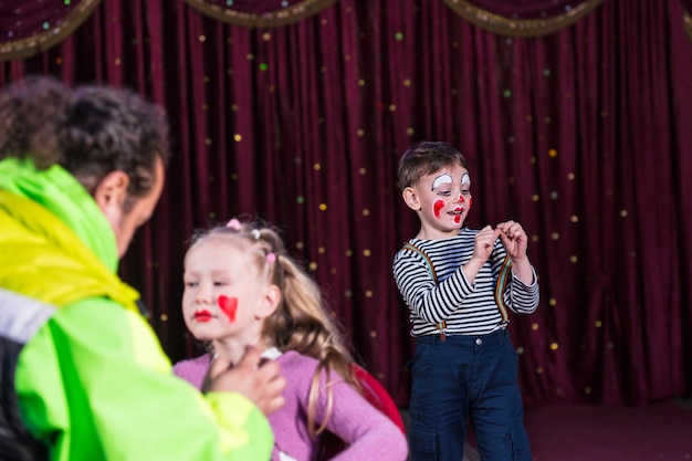 Menino vestido de palhaço usando maquiagem e camisa listrada se apresentando no palco com cortina vermelha, menina tendo maquiagem aplicada no rosto em primeiro plano