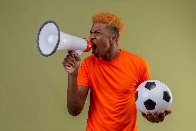 Menino vestindo uma camiseta laranja segurando uma bola de futebol gritando para o megafone com expressão de raiva no rosto em pé sobre a parede verde