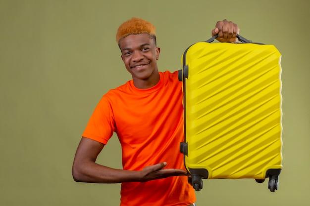 Menino vestindo uma camiseta laranja segurando uma mala de viagem e apresentando-a com o braço da sua mão sorrindo, positivo e feliz em pé sobre a parede verde