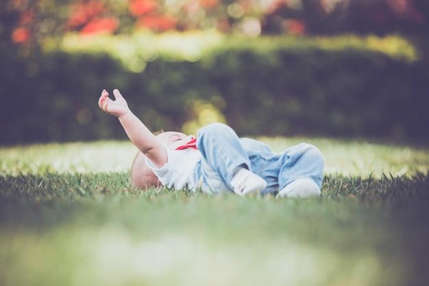 Menino vintage com suspensor vermelho no exterior - deitado na grama