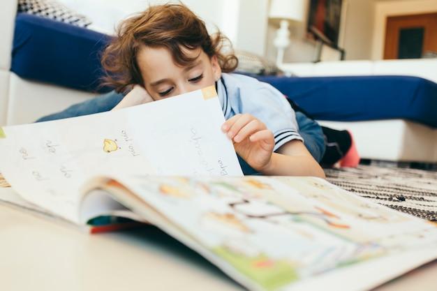 Menino virando páginas de livro didático