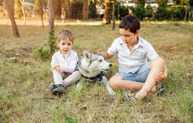 Meninos abraça amorosamente seu cachorro de estimação. crianças e um animal de estimação em um prado de verão. família brincando com o cachorro no parque.