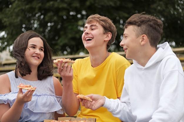 Meninos adolescentes e uma menina compartilhando lanches ao ar livre