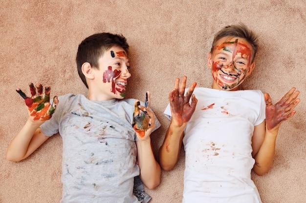 Meninos alegres com tinta no rosto e as mãos no chão e rindo.