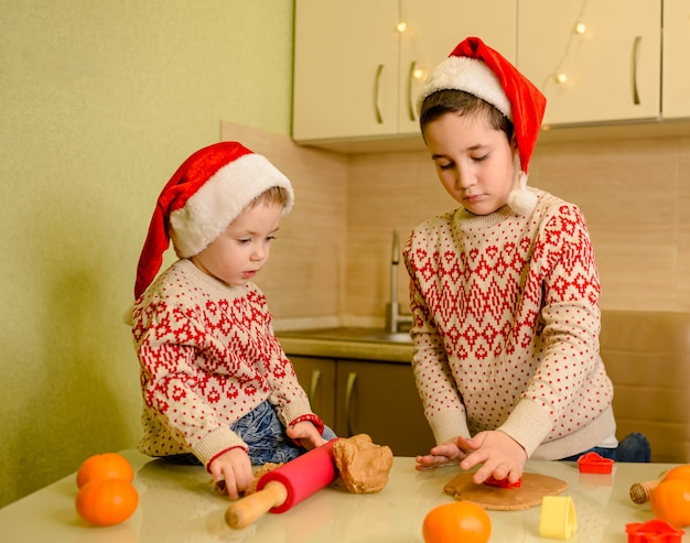 Meninos assam biscoitos de gengibre artesanais