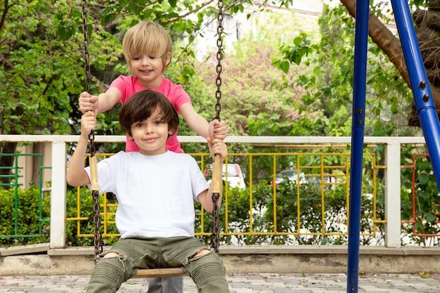 Meninos bonitos adoráveis no quintal balançando nos balanços