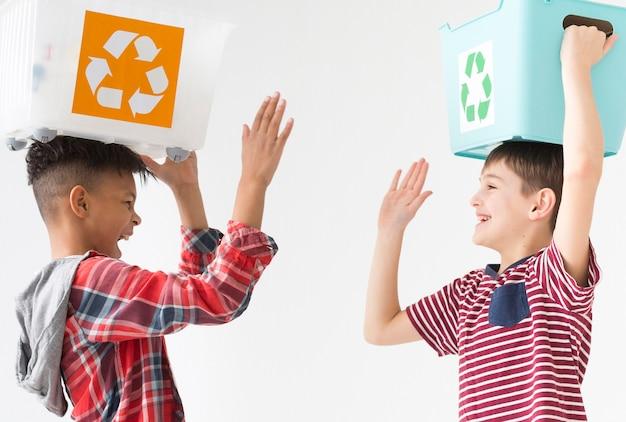 Meninos bonitos jovens felizes em reciclar juntos
