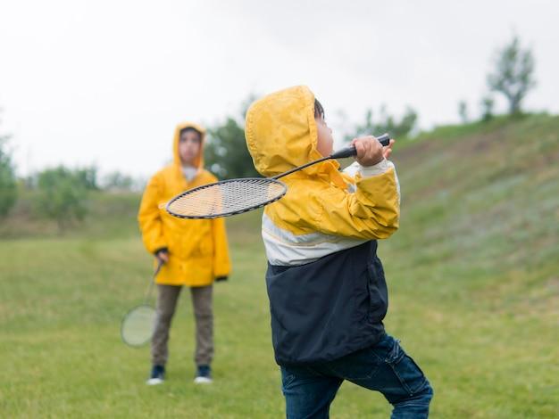 Meninos bonitos na capa de chuva jogando badminton