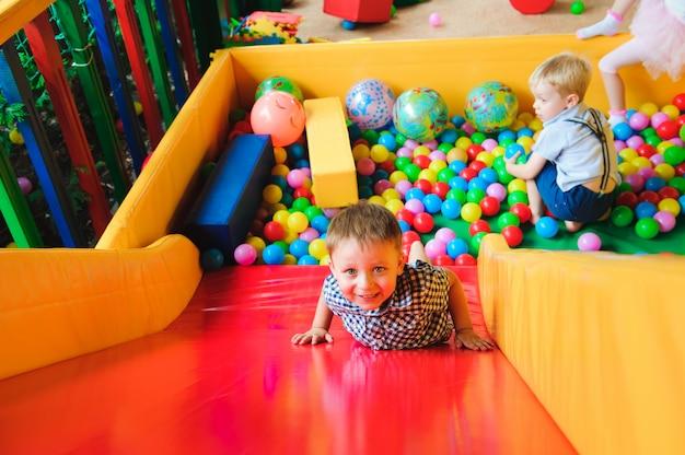 Meninos brincando no playground, no labirinto infantil com bola