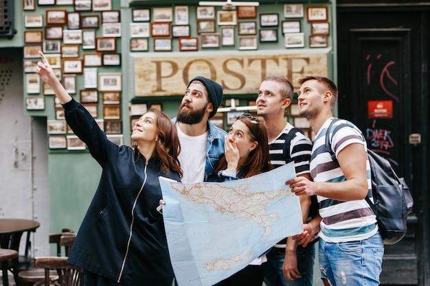 Meninos com bolsas e meninas com um mapa turístico observam algo em algum lugar da cidade velha