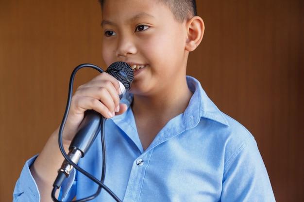 Meninos com microfone aprendendo a cantar